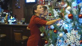 Two friends decorating a Christmas tree stock footage