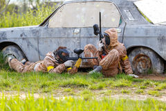 Two friends defend old car in paintball mission Royalty Free Stock Photo