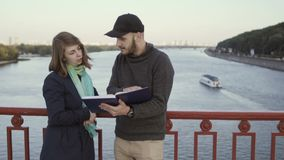 Two friends discuss book at the bridge. Young attractive brown-haired girl and handsome brunet man are outdoors at the bridge. Man holds the book in his hands stock footage