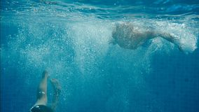 Two friends dive into the pool. Underwater footage two friends dive into the pool stock footage