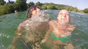 Two friends dives in and out of the water making funny faces. Close up of a young man and girl diving in and out of the water making funny faces, slow motion stock video footage