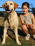 Two friends a dog and a little girl outdoor. Two friends a Labrador Retriever and a little girl outdoor Royalty Free Stock Image