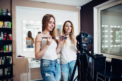Two friends doing a makeup products review shooting a video blog standing in front of camera Royalty Free Stock Image