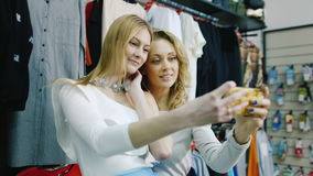 Two friends doing selfie in a clothing store. Smile, successful and happy shopping stock video footage