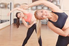 Two friends doing stretching exercises in gym Stock Photo