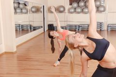 Two friends doing stretching exercises in gym. Stretching out. Portrait of two beautiful women doing well stretching exercises in gym Royalty Free Stock Photography