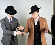 Two friends dressed in vintage clothes and depict retro detectives and spies in English classic style on a white studio background.  stock photo