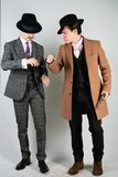 Two friends dressed in vintage clothes and depict retro detectives and spies in English classic style on a white studio background.  royalty free stock photos