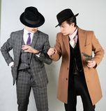 Two friends dressed in vintage clothes and depict retro detectives and spies in English classic style on a white studio background.  stock photos