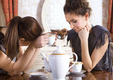 Two friends drink tea. Two girl-friends talk and drink tea in drawing room stock image