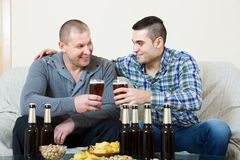 Two friends drinking beer at home Stock Photography