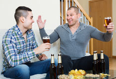 Two friends drinking beer at home Royalty Free Stock Photo
