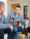 Two friends drinking beer at home Royalty Free Stock Photography