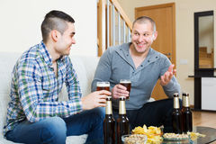 Two friends drinking beer at home Stock Image