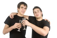 Two friends drinking champagne. Two friends holding two champagne glasses to celebrate an event Stock Images