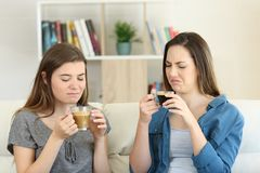 Two friends drinking coffee with bad flavour. Sititng on a couch in the living room at home royalty free stock photos