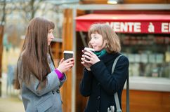 Two friends drinking coffee outdoors Royalty Free Stock Photos