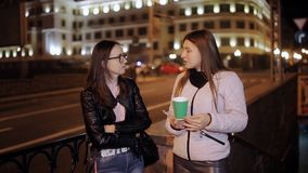 Two friends drinking coffee and talking in the night city stock video