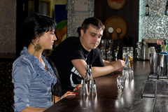 Two friends drinking vodka eye the last glass. Two friends drinking vodka shots sitting at the counter in the bar eye the last full glass as they decide who will stock photography