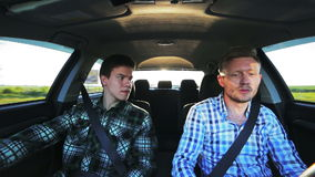 Two friends driving in the car, smiling, dancing in a sunny summer day stock video footage