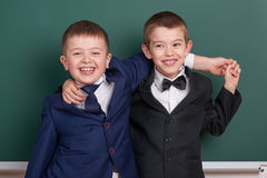 Two friends, elementary school boy near blank chalkboard background, dressed in classic black suit, group pupil, education concept Royalty Free Stock Photography
