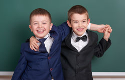Two friends, elementary school boy near blank chalkboard background, dressed in classic black suit, group pupil, education concept Stock Photography
