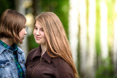 Two friends enjoy the summer sun against the trees royalty free stock images