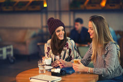 Two friends enjoying coffee together in a coffee shop Royalty Free Stock Photo