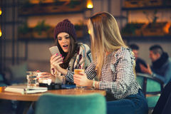 Two friends enjoying coffee together in a coffee shop Stock Image