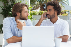 Two friends enjoying coffee together with laptop Stock Image