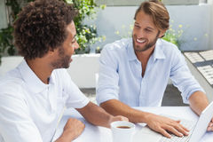 Two friends enjoying coffee together with laptop Stock Images