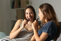 Two friends enjoying eating chocolate in the night. Sitting on a couch in the living room at home royalty free stock photos