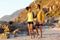 Two friends enjoying a walk on the beach Stock Photos