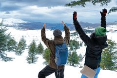 Two friends enjoying winter holidays. Two happy friends enjoying winter holidays, men and women standing with raised up hands in the mountains, enjoying Stock Photography
