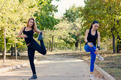 Two friends exercising together in a park Stock Images