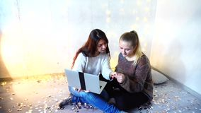 Beautiful dark-haired girl working on laptop at home christmas. Two friends exploring internet looking for job, using laptop at home decorated for christmas. New stock footage