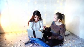 Beautiful dark-haired girl working on laptop at home christmas. Two friends exploring internet looking for job, using laptop at home decorated for christmas. New stock video