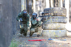 Two friends in extreme paintball training with capturing flags. Royalty Free Stock Image