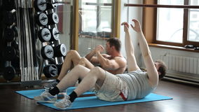 Two friends, fat guy and athlete, train abdominal muscles. Tubby man came to the gym for the first time, because it fell in love with a beautiful girl and stock video footage