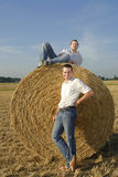 Two friends in a field with straw bales Royalty Free Stock Photos