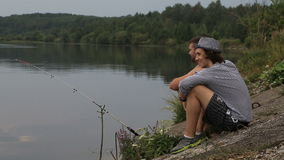 Two friends on a fishing. Trip drink soft drinks and talk stock video footage