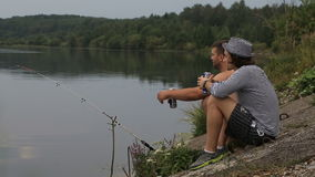 Two friends on a fishing. Trip drink soft drinks and talk stock footage