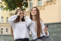 Two friends fooled showing grimaces. They both have long brown hair that is long to the waist and they are dressed in identical white sweaters Stock Images