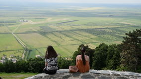 Two friends girlfriends,sisters talking on the high lookout, plain in the background stock video footage