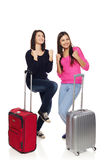 Two friends girls with travel suitcases. Two excited girls friends in full length with travel suitcases celebrating success, isolated on white background Royalty Free Stock Image