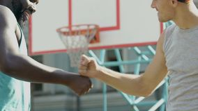 Two friends greeting each other making cool handshake before basketball game. Stock footage stock video footage