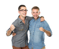 Two friends guys standing with hands on shoulders and looking at. A portrait of two friends guys standing with hands on shoulders and looking at you  on white Royalty Free Stock Photo