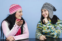 Two friends have a conversation. Two women friends  in winter clothes having an conversation and sitting at table,they laughing and gesturing  and looking each Royalty Free Stock Photo
