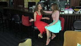 Two friends have fun at the cafe. Beautiful girls talk, chat and laugh stock video