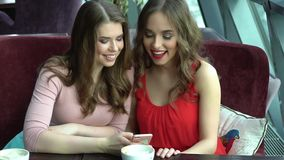 Two friends have fun at the cafe. Beautiful girls talk, chat and laugh stock footage